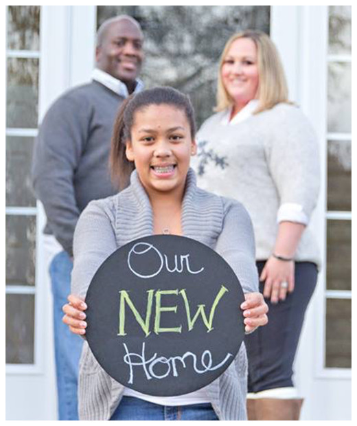 Family in front of their new home
